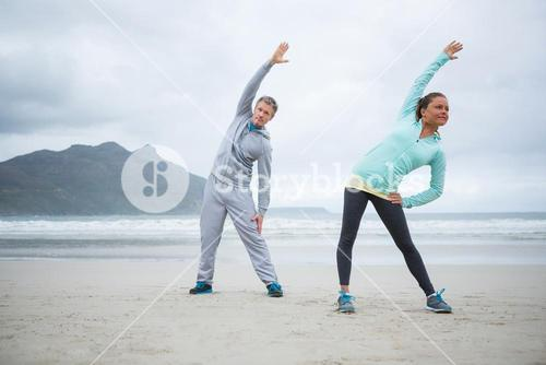 Couple performing stretching exercise on beach