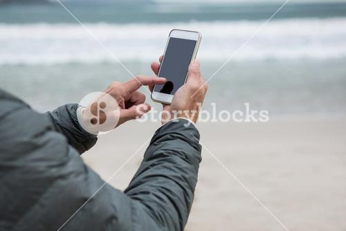 Man using mobile phone on beach