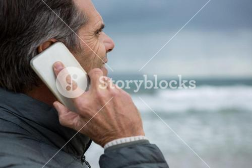 Man talking on mobile phone on beach