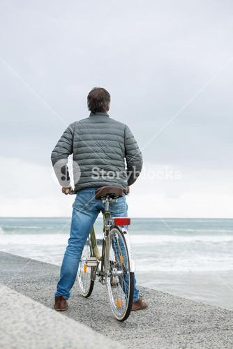Rear view of man standing on bicycle