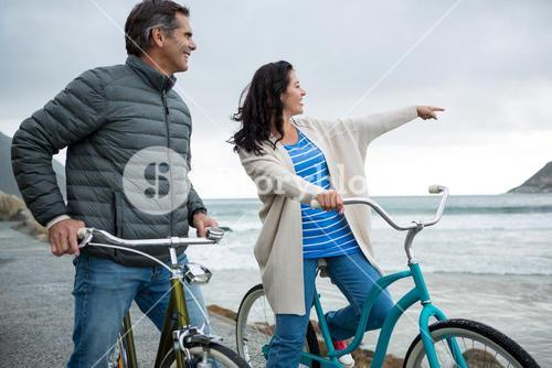 Happy couple on bicycle pointing at distance on beach