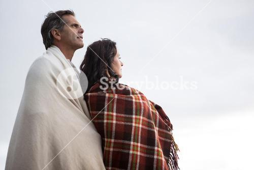 Thoughtful couple wrapped in shawl standing on beach