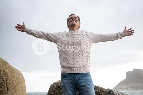 Happy man standing with arms outstretched