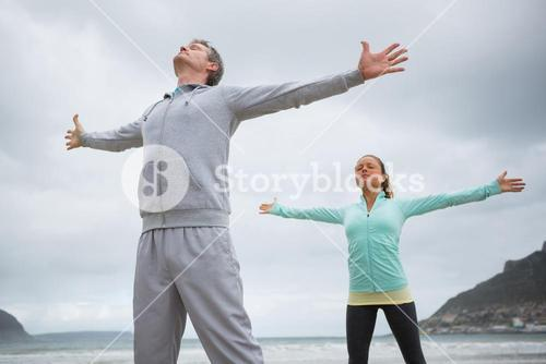 Couple standing with arms outstretched on beach