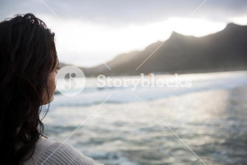 Thoughtful woman standing on beach