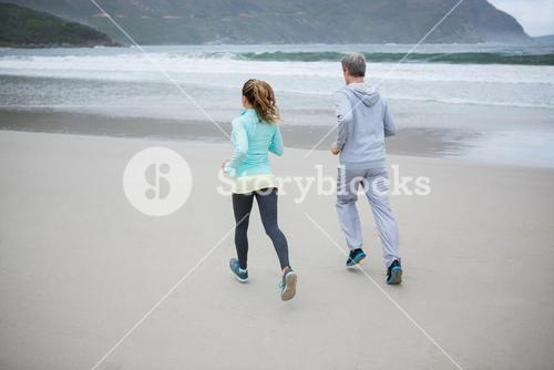 Rear view of couple jogging on beach