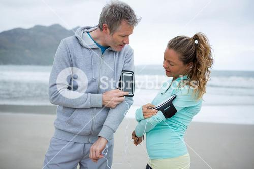 Couple using mobile phone while listening music on beach