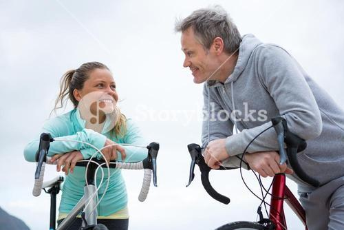 Couple leaning on bicycle while interacting with each other
