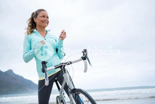 Happy woman standing with bicycle on beach