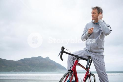 Man standing with bicycle listening music on headphones at beach