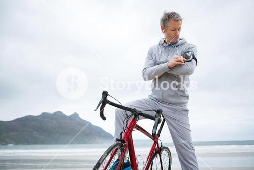 Man with bicycle listening music on mobile phone at beach