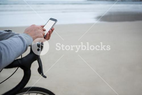 Close-up of man hand on bicycle using mobile phone