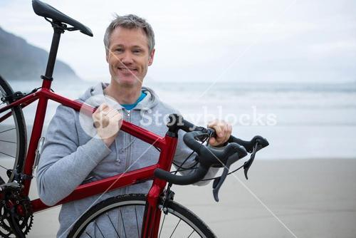Man carrying bicycle on beach