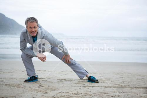 Man performing stretching exercise on beach