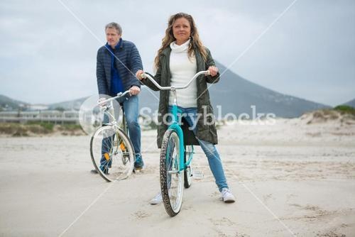 Couple standing with bicycle on beach