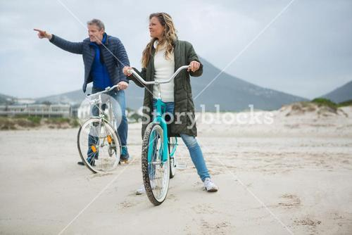 Couple on bicycle pointing at distance on beach
