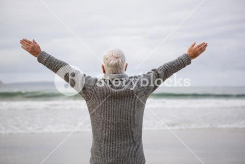 Rear view of senior man standing with arms outstretched on beach