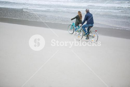Couple riding bicycle on beach