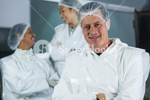 Smiling butcher standing with arms crossed