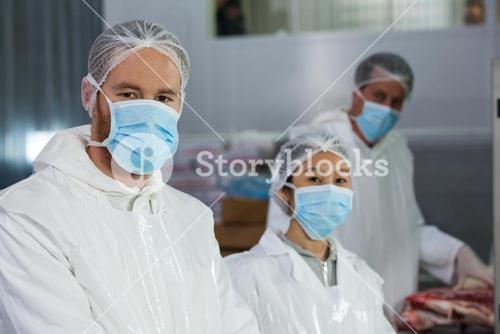 Butchers in protective workwear at meat factory