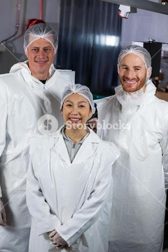 Team of butcher standing in meat factory