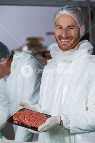 Butcher holding raw meat patties arranged in tray