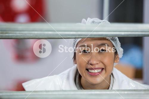 Female butcher standing in meat factory