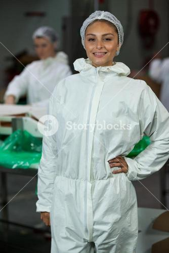 Female butcher standing with hands on hip