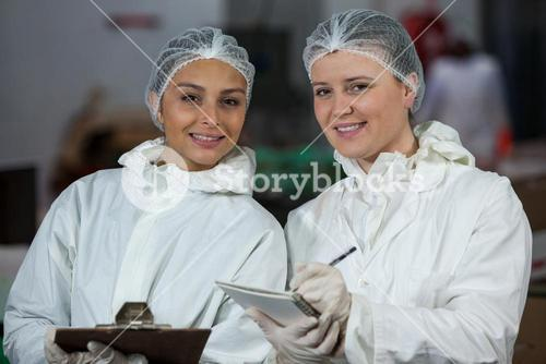 Female butchers holding clipboard and diary