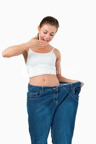 Portrait of a suprised woman wearing too large jeans