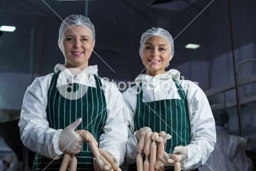 Female butchers processing sausages