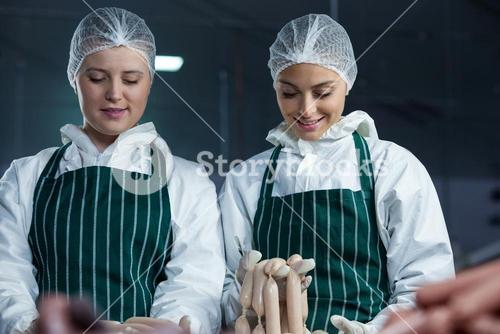 Female butcher processing sausages