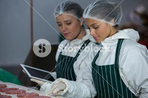 Female butchers maintaining records over digital tablet