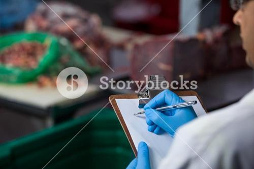 Technicians maintaining records on clipboard