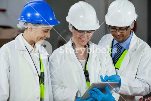Technicians discussing over digital tablet