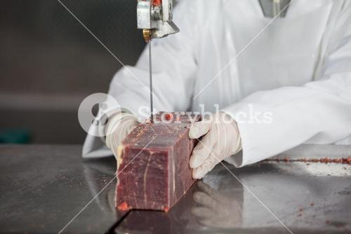 Female butcher cutting raw meat on a band saw machine