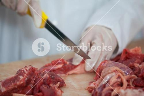 Butcher cutting meat at meat factory