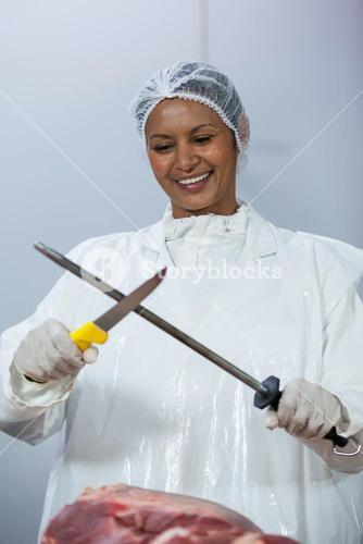Female butcher sharpening her knife