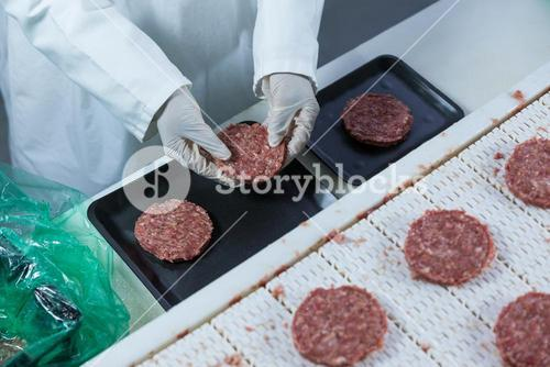 Butcher arranging hamburger patty on tray