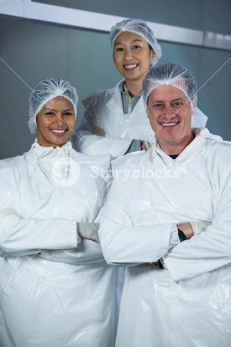 Team of butchers standing with arms crossed