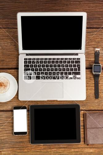 Laptop, smartwatch, smartphone and digital tablet with cup of coffee