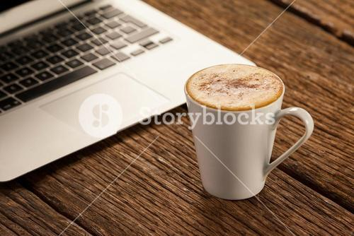 Laptop and cup of coffee on wooden table