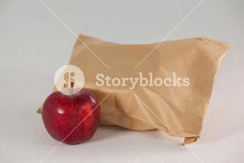 Brown paper lunch bag with red apple