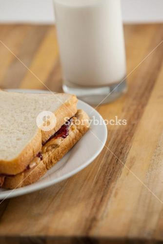 Peanut butter and jam sandwich on plate