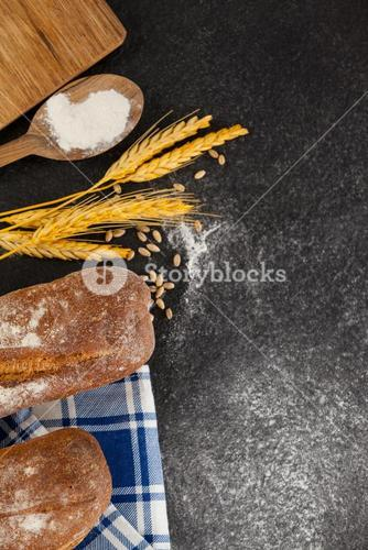 Bread loaf with wheat grains and flour
