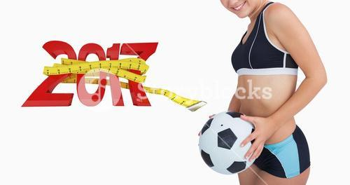 Composite image of portrait of happy woman in sportswear with football