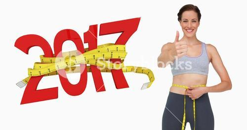 Composite image of fit woman measuring waist while gesturing thumbs up