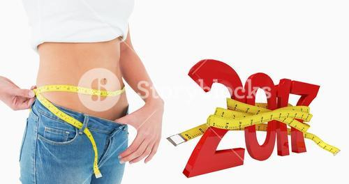 Composite image of mid section of a woman measuring waist in a big sized jeans