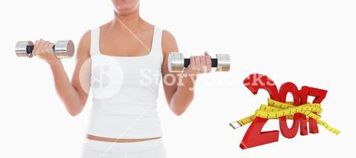 Composite image of midsection of woman exercising with dumbbells