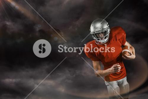 Composite image of american football player in red jersey looking down while holding ball
